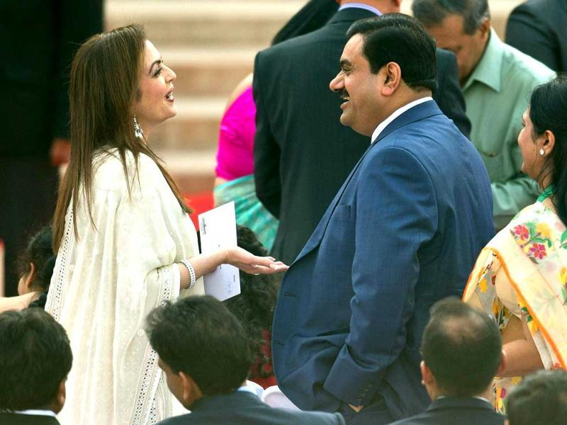 Businessman Gautam Adani talks with Neeta Ambani, wife of business magnate Mukesh Ambani, prior to the swearing-in ceremony for new Indian Prime Minister Narendra Modi. (AFP)