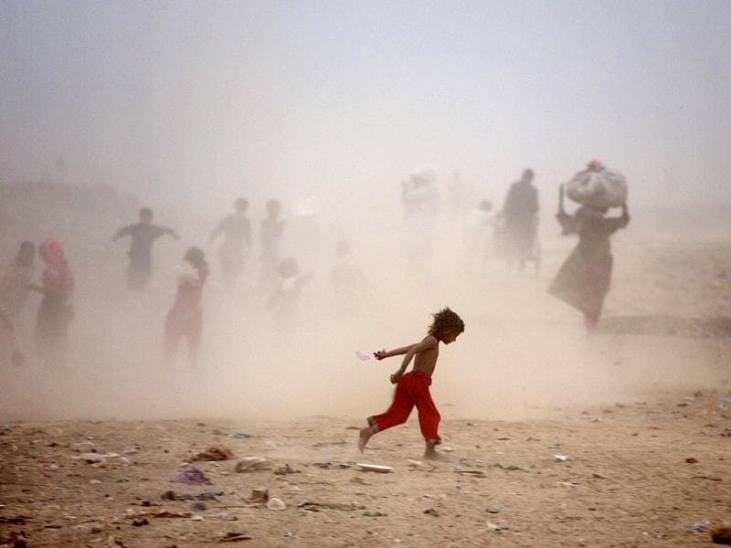Pakistanis run as they get caught in a sand storm on the outskirts of Islamabad, Pakistan. (AP Photo)