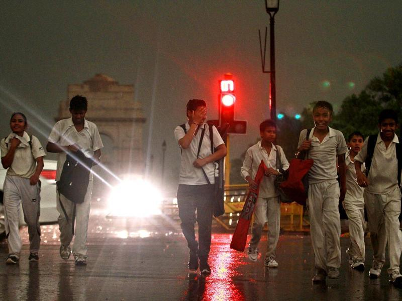Students get caught in the sudden rain in the evening in New Delhi. (photo by Arun Sharma/ Hindustan Times)