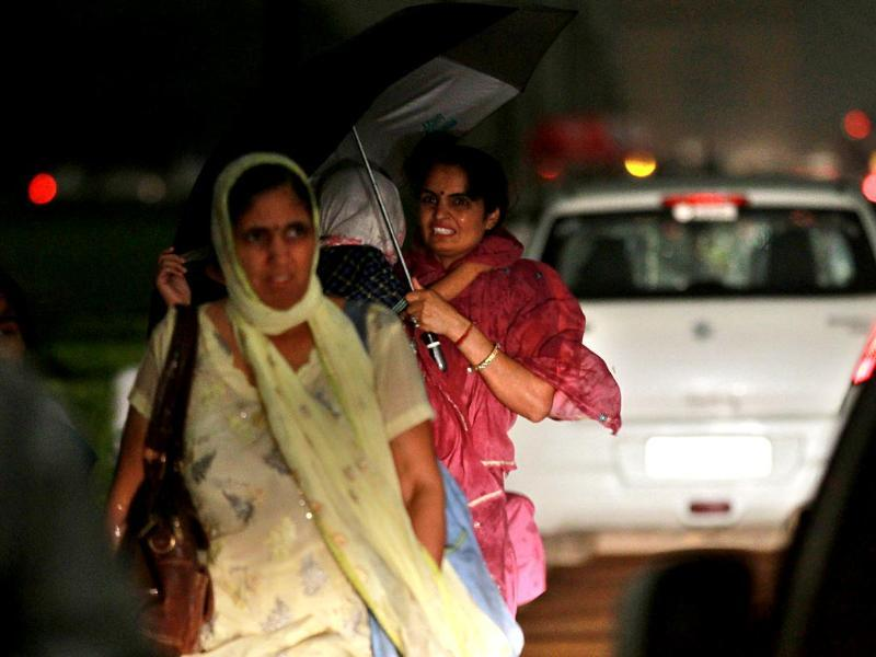 Delhiites were caught in the sudden rain that lashed New Delhi on Friday evening. (Photo by Arun Sharma/ Hindustan Times)