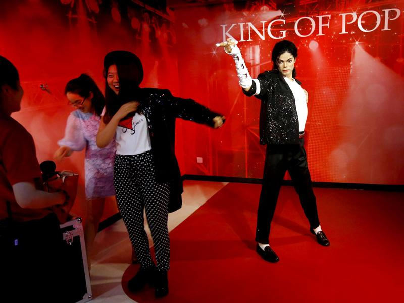 A visitor tries on a similar jacket of late US pop star Michael Jackson, whose wax figure is displayed at the Madame Tussauds museum in Beijing, China. (EPA Photo)