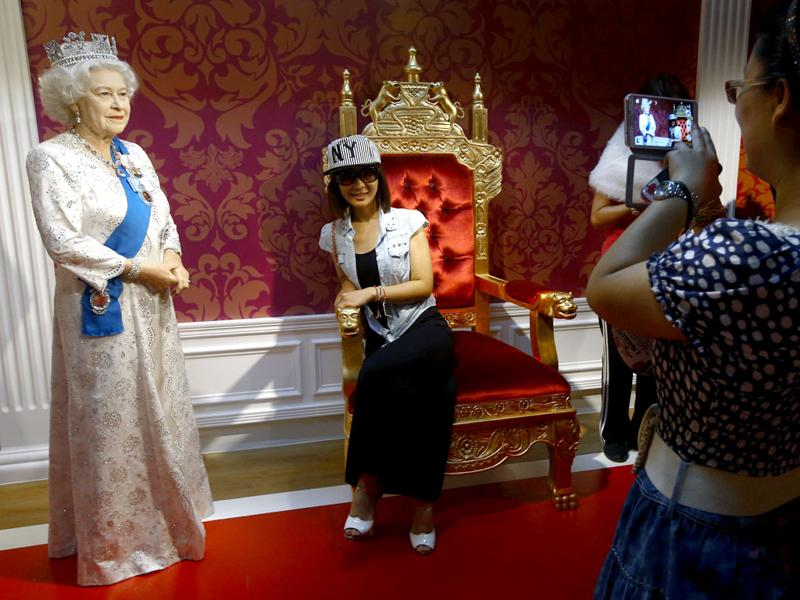 Visitors take souvenir photos beside a wax figure of Britain's Queen Elizabeth II displayed at the Madame Tussauds museum in Beijing, China. (EPA Photo)