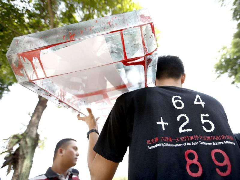 A protester carries a model of tank during a protest in front of the Chinese Embassy in Kuala Lumpur, Malaysia. A group of protesters staged a rally to mark the 25th anniversary of the Chinese military crackdown on the pro-democracy movement in Beijing's Tiananmen Square. The numbers in the shirt stands for