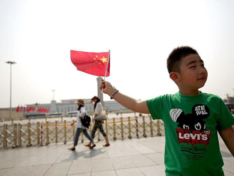 A boy poses with a Chinese national flag in front of Tiananmen Square in Beijing. From keeping foreign reporters off Beijing's Tiananmen Square to widespread censorship of the Internet, China marked 25 years since the bloody suppression of pro-democracy protests under a cloak of security. (Reuters)