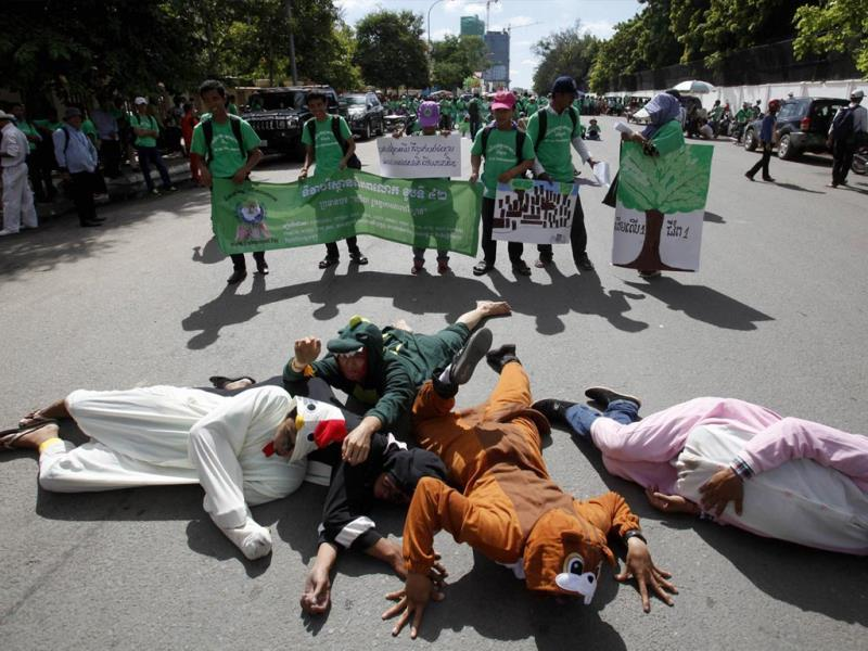 People perform as they march along a street in Phnom Penh. World Environment Day is celebrated on June 5 to raise worldwide awareness for environmental protection and motivate action towards a cleaner and greener future, according to the United Nations Environment Programme website. The signs read,