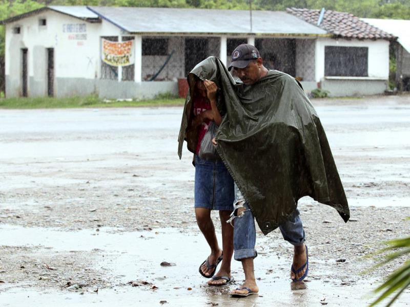 Residents use a poncho to shelter from rain caused by Tropical Depression Boris in Santo Domingo Zanatepec, on the outskirts of Oaxaca. Tropical Storm Boris drew closer to the southern Pacific coast of Mexico, churning northward toward the largest refinery of national oil company Pemex, Salina Cruz. (Reuters)