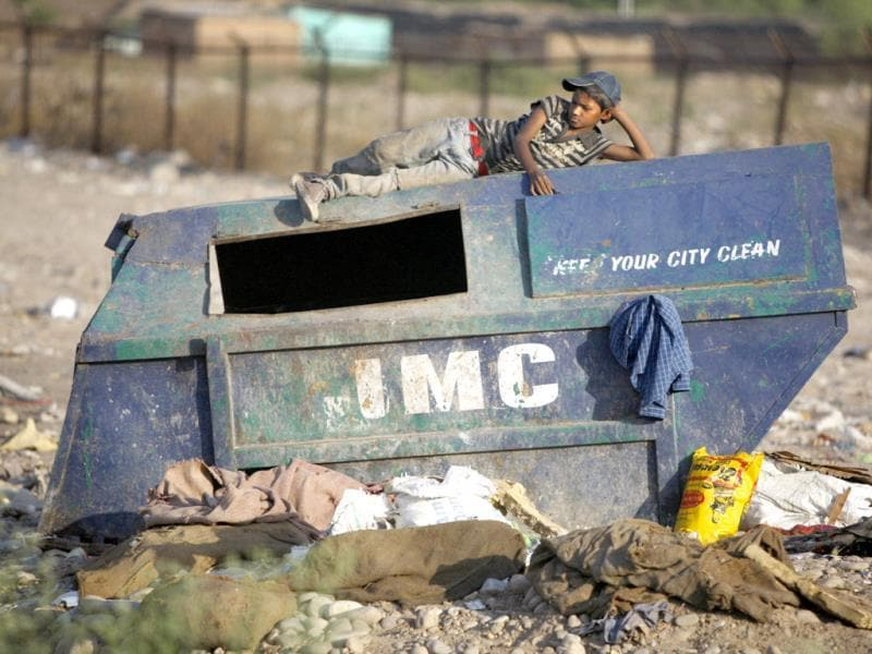 A rag picker rests on a garbage dump container on World Environment Day, on the outskirts of Jammu. World Environment Day is celebrated every year on June 5 by the United Nations to stimulate global awareness on environmental issues. (AP photo)