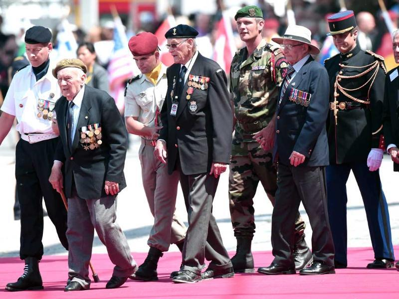 WWII veterans are escorted by soldiers as they arrive to attend the international D-Day commemoration ceremony on the beach of Ouistreham, Normandy, on June 6, 2014, marking the 70th anniversary of the World War II Allied landings in Normandy. (AFP Photo)