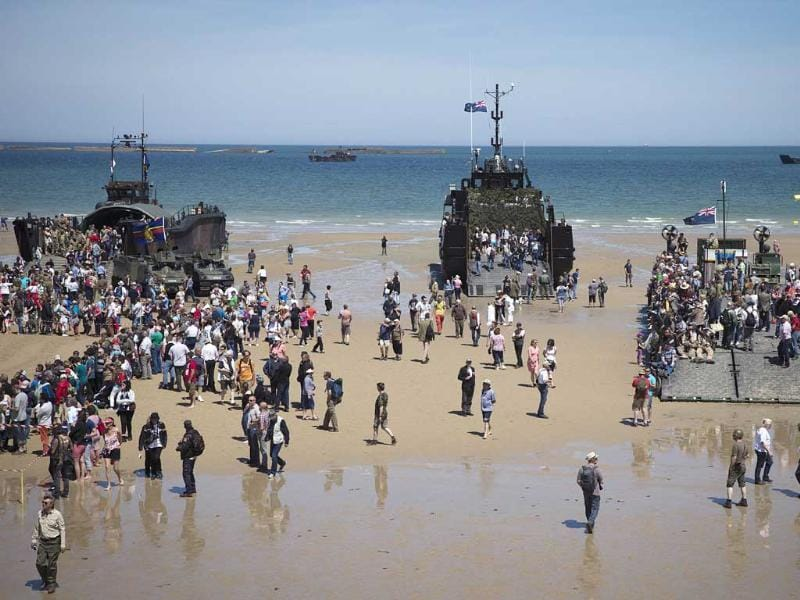 People visit World War II landing crafts on the Arromanches beach, Normandy, on June 6, 2014 during the ceremonies marking the 70th anniversary of the Operation Overlord. The D-Day ceremonies on June 6 this year mark the 70th anniversary since the launch of 'Operation Overlord', a vast military operation by Allied forces in Normandy, which turned the tide of World War II, eventually leading to the liberation of occupied France and the end of the war against Nazi Germany. (AFP Photo)