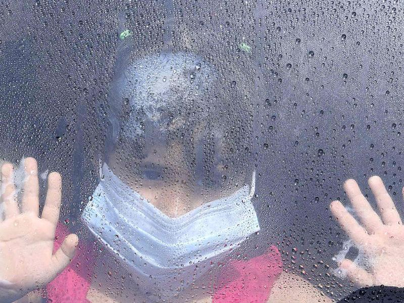 A girl wearing a mask looks out a car window as rain drops are seen in Taif. (Reuters Photo)