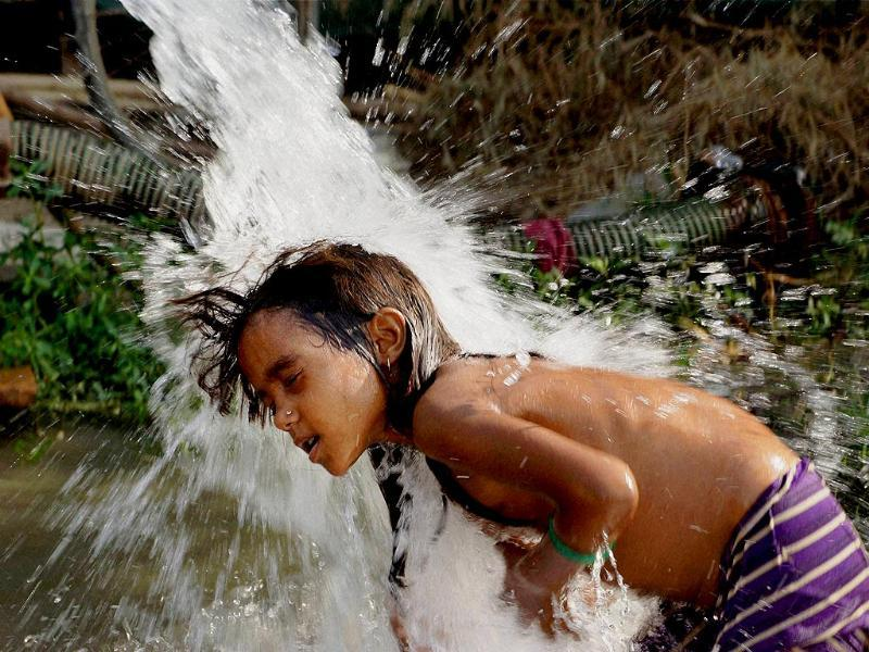 A girl takes shower under a tube well to beat the heat as mercury soars in New Delhi. (PTI Photo)