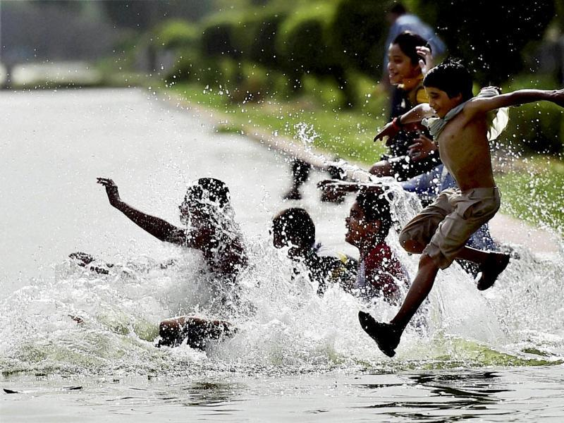 Youngsters take respite from the heat as mercury soars in New Delhi. (PTI photo)