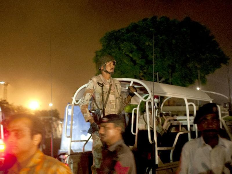 Pakistani security troops rush to Karachi airport terminal following attacks by unknown gunmen. (AP photo)