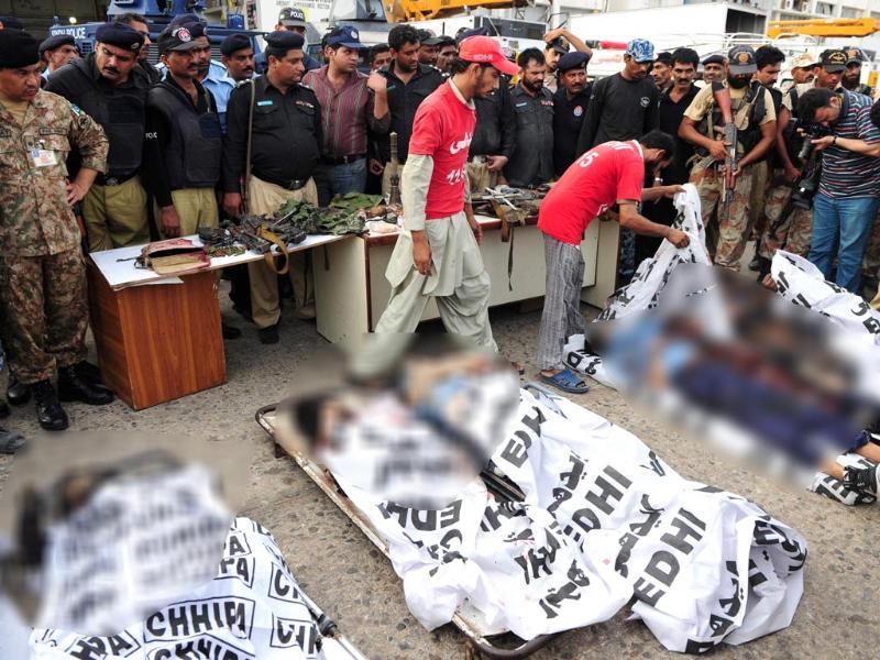 Pakistani security officials stand around the mortal remains of the suspected militants after the attack at the Jinnah International Airport, in Karachi (EPA photo)