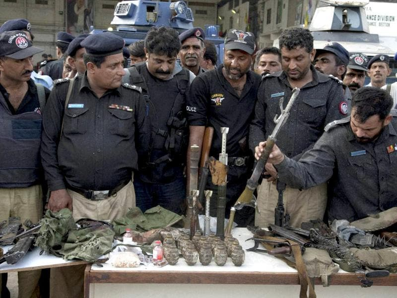 Pakistani police officers display ammunition confiscated from attackers at the Jinnah International Airport. (AP/PTI photo)
