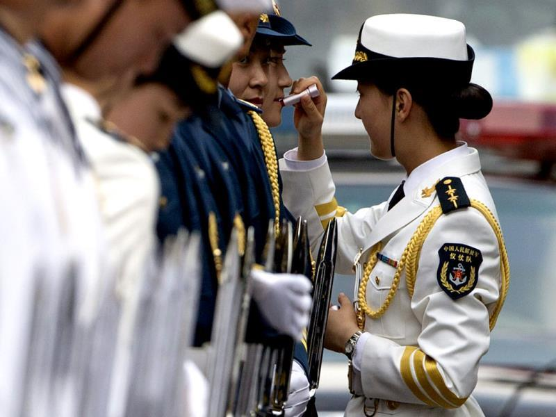 A female officer of the Chinese People's Liberation Army (PLA) Guard of Honor helps another guard to put on lipstick during their preparations for the welcome ceremony of Bangladesh Prime Minister Sheikh Hasina (not in photo) at the Great Hall of the People in Beijing. (EPA Photo)