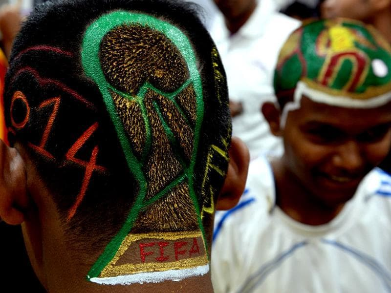 Football enthusiasts Nilesh Kadam (L) and Abhijit Chavan have FIFA World Cup-inspired scenes and the trophy logo painted into haircuts at a salon in Mumbai. (AFP Photo)