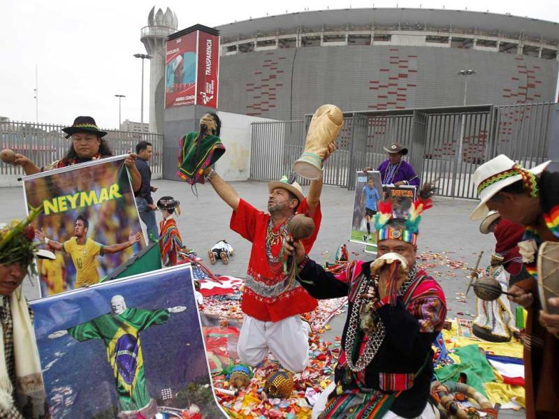 Peruvian shamans perform a ritual of predictions for the FIFA World Cup in Brazil, holding a World Cup trophy replica in front of the National Stadium of Peru, in Lima. (Reuters photo)