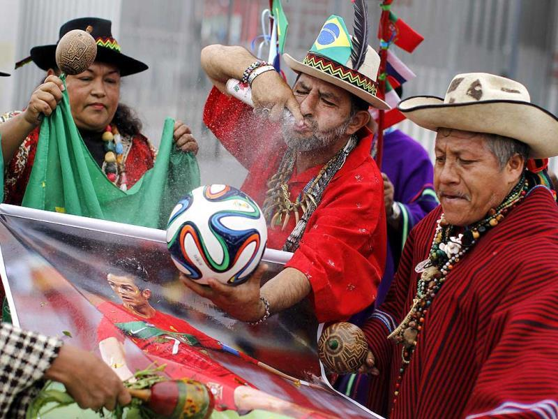 Peruvian shamans perform a ritual while holding a replica of the official ball for 2014 World Cup and a poster of Portugal's Cristiano Ronaldo.(Reuters photo)