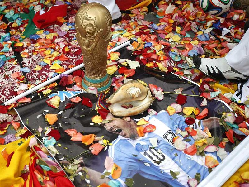 A poster of Argentina's Lionel Messi lies on the ground next to a World Cup trophy replica as shamans perform the ritual. (Reuters photo)