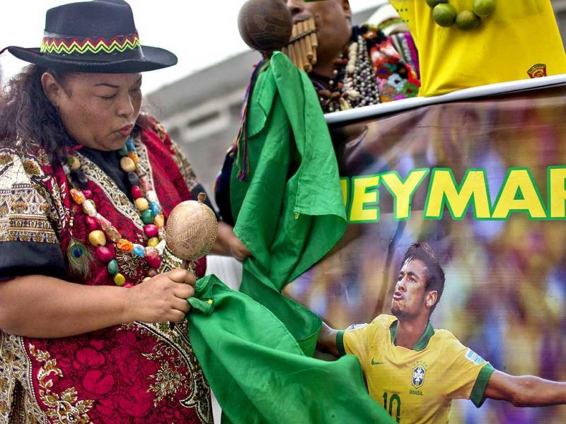 A shaman holds a poster of Brazil's Neymar. (AFP Photo)