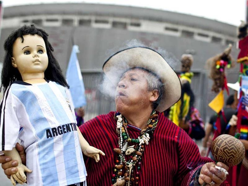 A shaman carries a doll wearing an Argentinian jersey. (AFP Photo)
