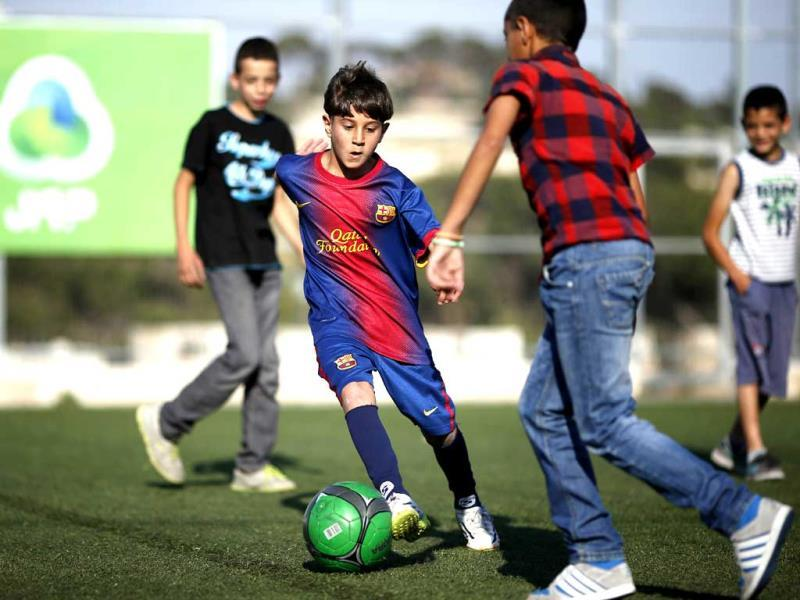 Palestinian Ahmad Salaymah, considered a lookalike of Argentinian football star Lionel Messi, plays in the Old City of Jerusalem. (AFP Photo)