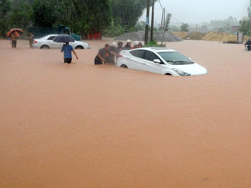 Rescuers try to move a car trapped on a flooded street in Qinzhou, southwest China's Guangxi province. (AFP Photo)