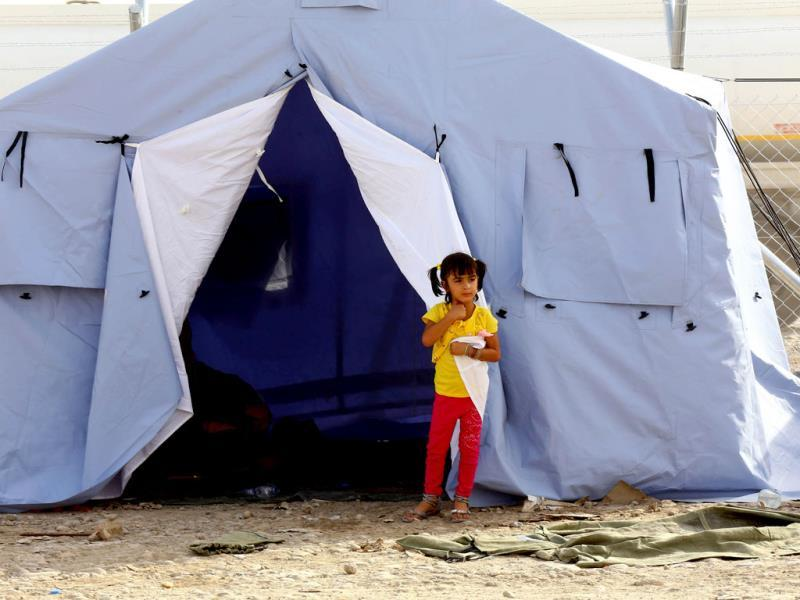 An Iraqi refugee girl from Mosul stands outside her family's tent at Khazir refugee camp outside Irbil, 217 miles north of Baghdad. (AP Photo)
