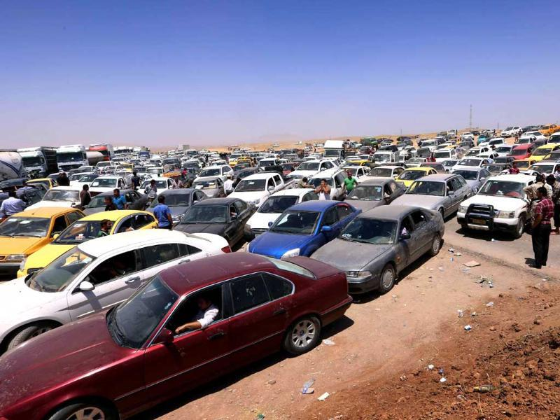 Iraqis fleeing violence in the Nineveh province wait in their vehicles at a Kurdish checkpoint in Aski kalak, 40 kms West of Arbil, the capital of the autonomous Kurdish region of northern Iraq. (AFP photo)