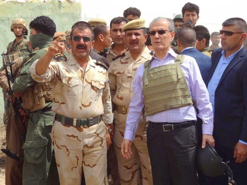 Kirkuk province's Kurdish governor Najim al-Din Omar Karim, wearing a bullet-proof vest and holding a helmet in his hand, listens to a commander of the Peshmerga forces as their troops were being deployed on the main road between Kirkuk, Mosul. (AFP photo)