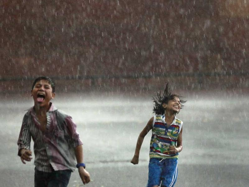 People enjoy the rain after a long spell of heat wave at Red fort area in New Delhi. (Photo by Raj K Raj/ Hindustan Times)