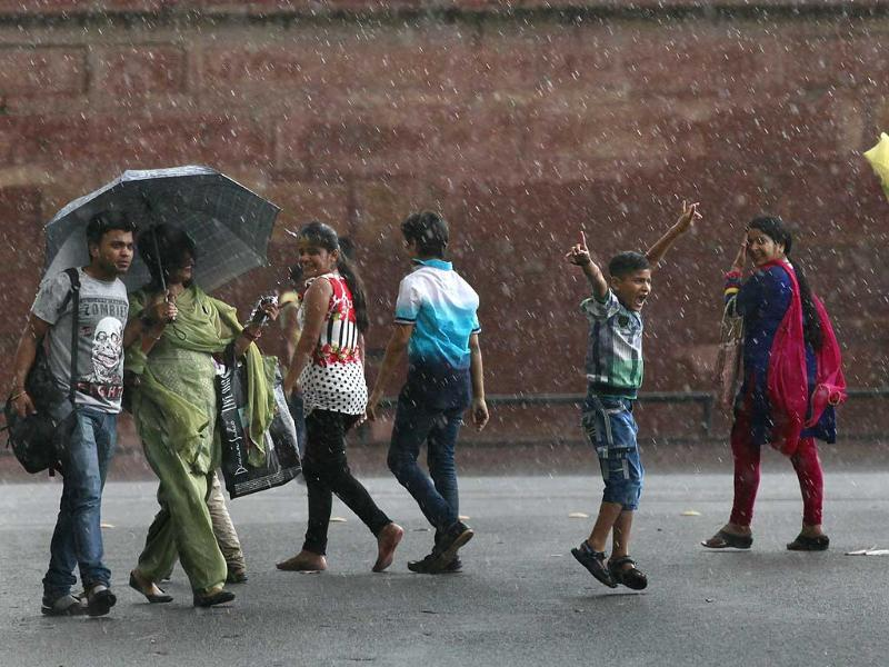 People enjoy the rain in New Delhi on Thursday evening. (Photo by Raj K Raj/ Hindustan Times)