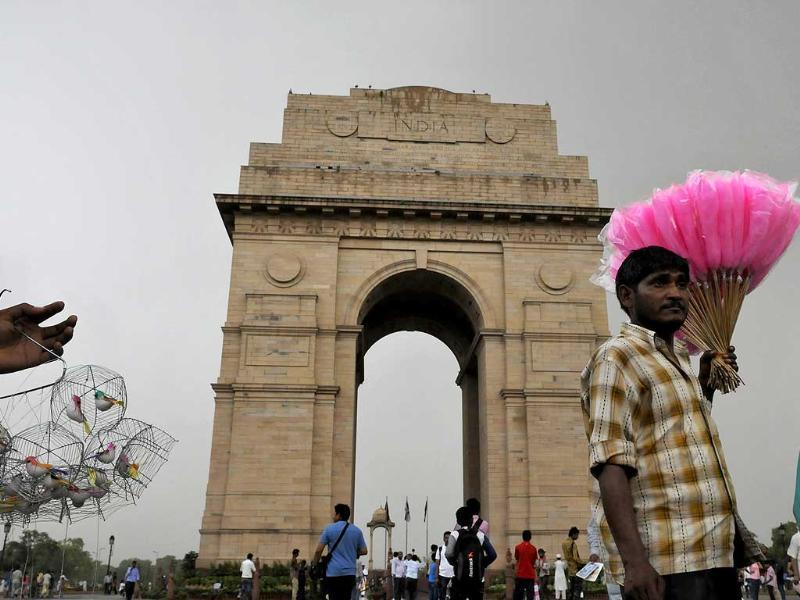 A candyman sells his ware as people thronged to the India Gate area after the mercury dipped after a long wait with wind and rain in New Delhi. (Photo by Saumya Khandelwal/ Hindustan Times)