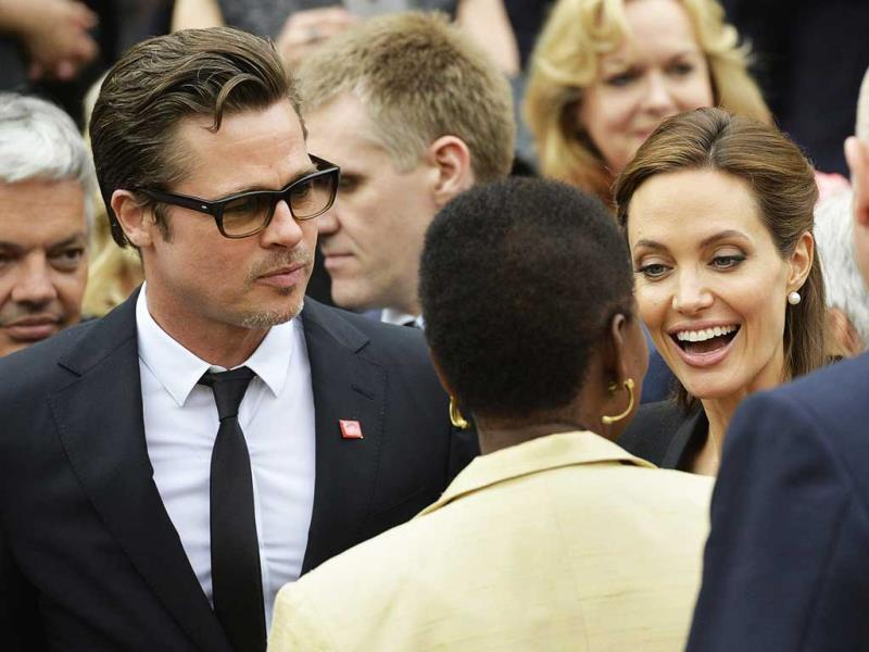 Angelina Jolie and Brad Pitt talk to a delegate after a family photo at Lancaster House on the third day of the Global Summit to End Sexual Violence in Conflict.  AFP Photo