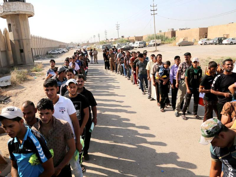 Iraqi men line up at the main army recruiting center to volunteer for military service in Baghdad, Iraq, after authorities urged Iraqis to help battle insurgents. (AP Photo)
