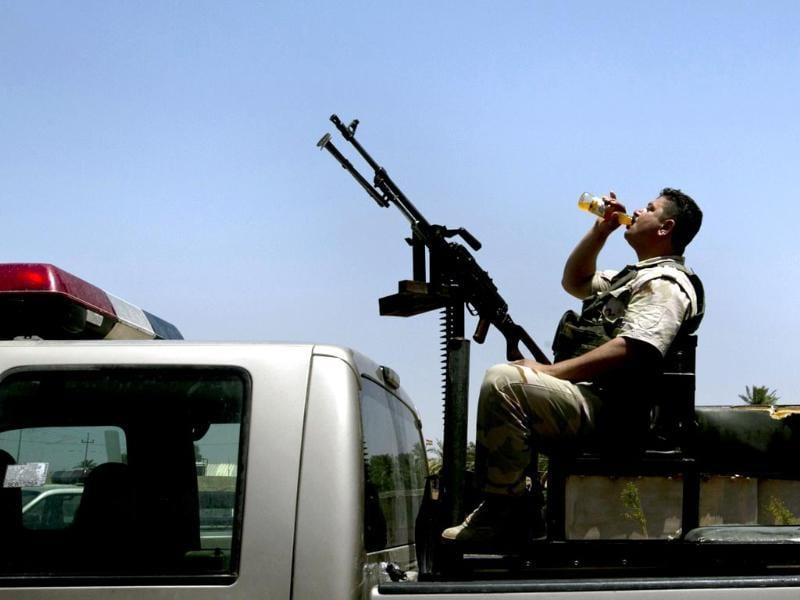 An Iraqi Kurdish soldier drinks from a bottle as he sits at the back of a truck at an operating base in Iraq's Diyala province whilst waiting to deploy into into Jalawla to fight militants of the ISIL. (AFP Photo)