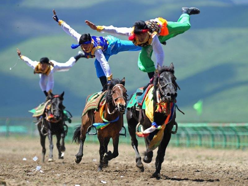 China, Aba: June 17, 2014  Riders wearing ethnic group costume competing in a traditional horseback riding event in Hongyuan county of Aba town. Some 300 riders from 15 teams around the country took part in the traditional horseback riding event. (AFP PHOTO)