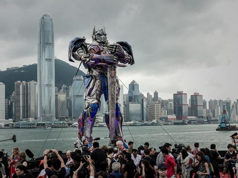 Hong Kong: June 19, 2014  People duck and hide themselves under umbrellas as a giant figure of Optimus Prime from the movie
