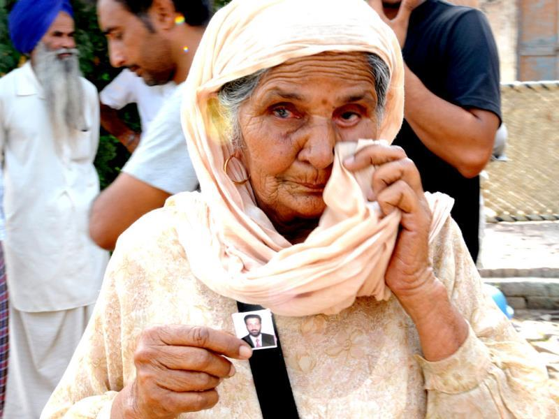 A Grandmother Beant Kaur of Sahib Singh, who were taken hostage in Iraq, showing photograph of his grandson at Khatuli village in Patiala District. (HT Photo)