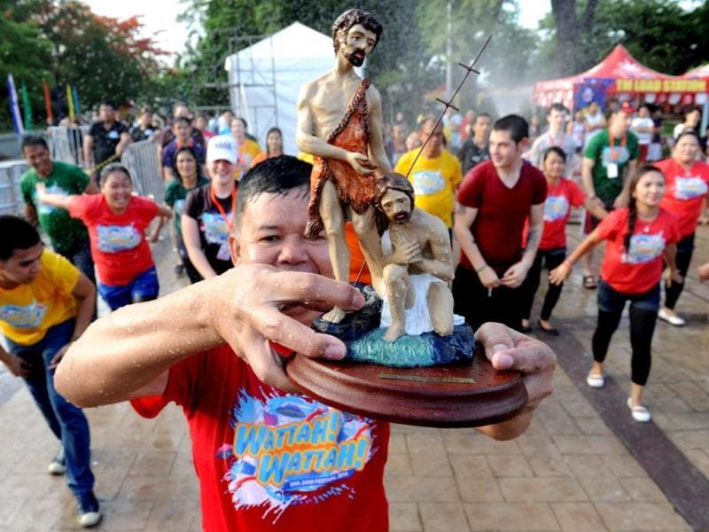 man holds up a religious icon of John the Baptist as residents (in background) are sprayed with water to celebrate the feast day of St John the Baptist in Manila. (AFP photo)