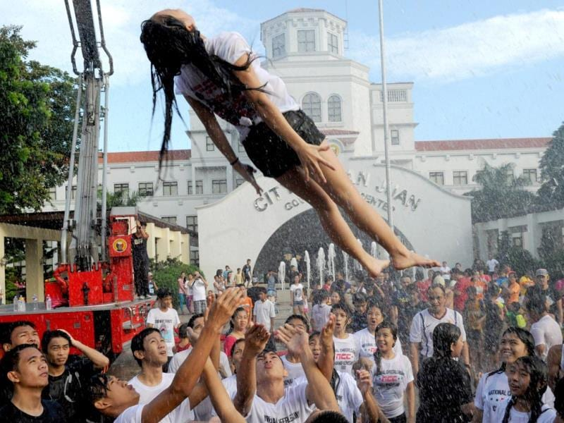 A woman hoisted into the air by friends after they were sprayed with water as residents celebrate the feast day of St John the Baptist in Manila. (AFP photo)