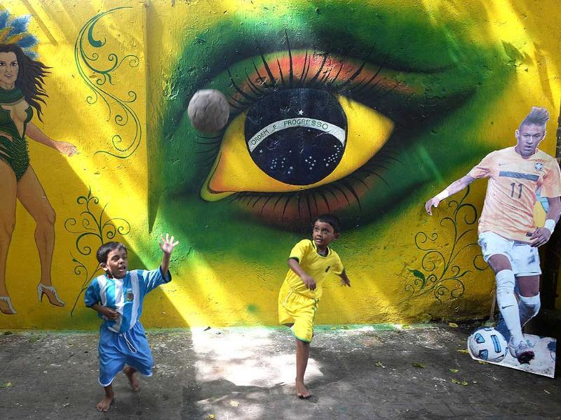 Young Indian children in Brazil (R) and Argentina football attire play in front of wall graffit supporting their favorite team Brazil, in Kolkata. (AFP Photo)