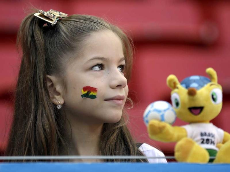 A young girl waits with the mascot 'Fuleco' for the start of the match between Portugal and Ghana in Brasilia, Brazil. (AP Photo)