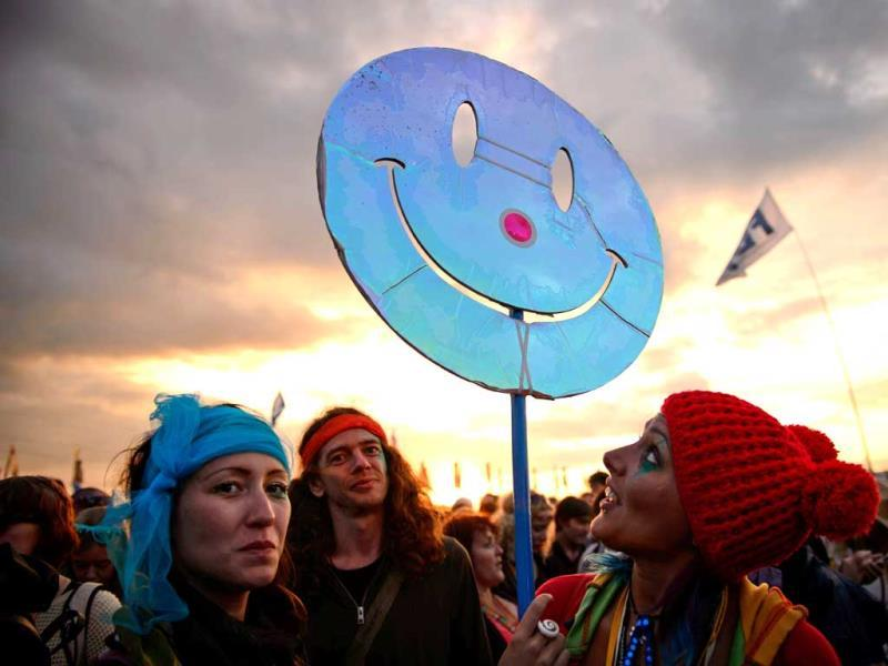 Revellers carry a smiley face sign through the crowds as the sun sets at the festival. (AFP photo)