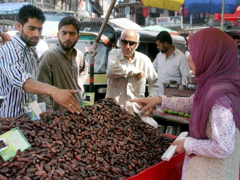 People buy dates from a vendor on the eve of the holy month of Ramadan in Srinagar. (PTI photo)