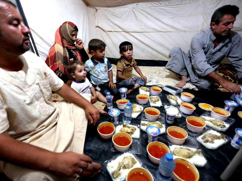 Displaced Iraqis ready to break their fast during the holy Muslim month of Ramadan, as they sit in a tent provided by the UN refugee agency at a temporary camp set up to shelter people fleeing violence in northern Iraq in Aski kalak, 40 kms west of the Kurdish autonomous region's capital Arbil. (AFP photo)