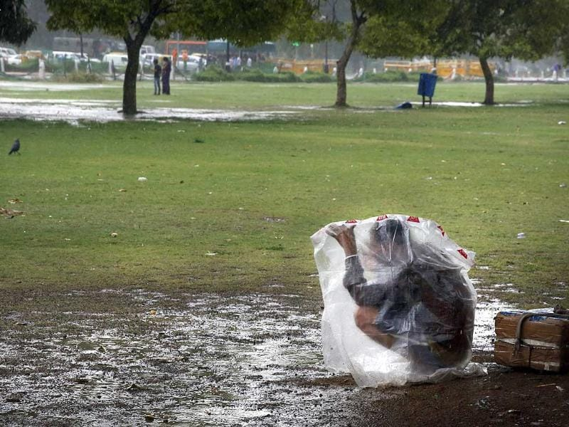 A man covers himself with a plastic sheet as it rains in New Delhi (AP Photo)