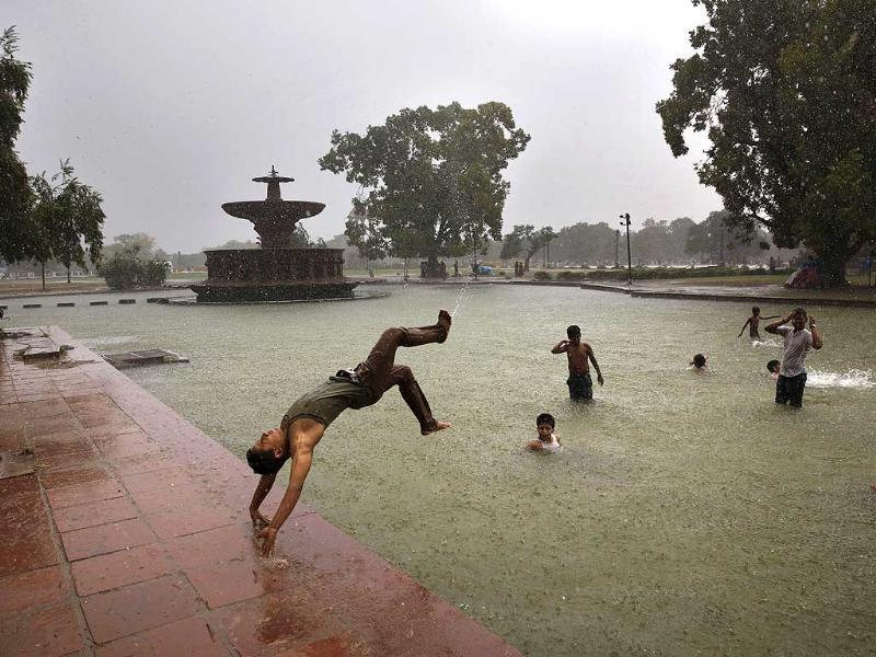 A boy somersaults into a water body as it rains in New Delhi (AP Photo)