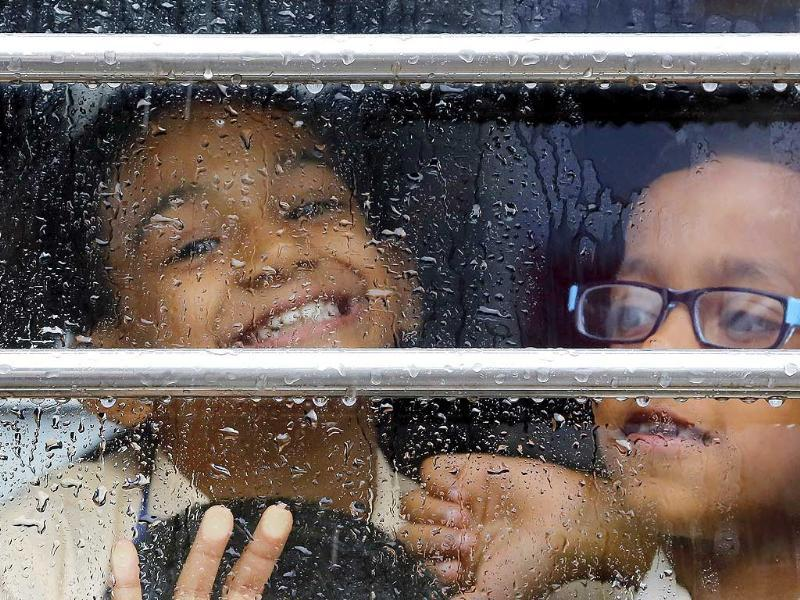 School children look out a window of a school bus as it rains in Mumbai (AP Photo)